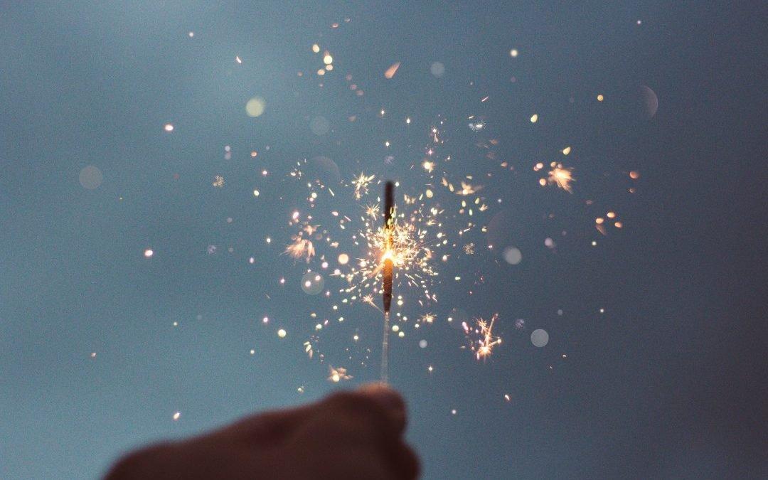 A hand holding a lit sparkler.