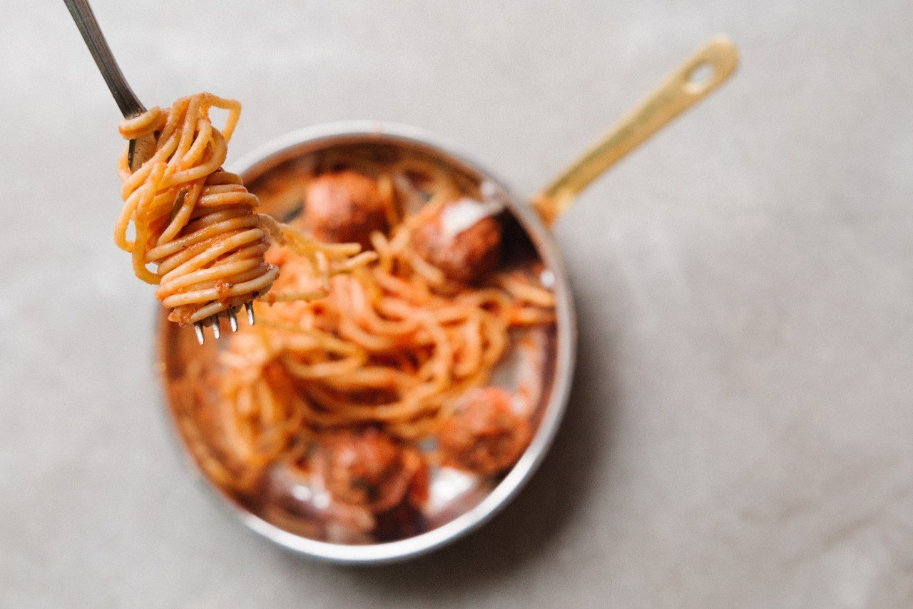 Spaghetti and meatballs in a pan.