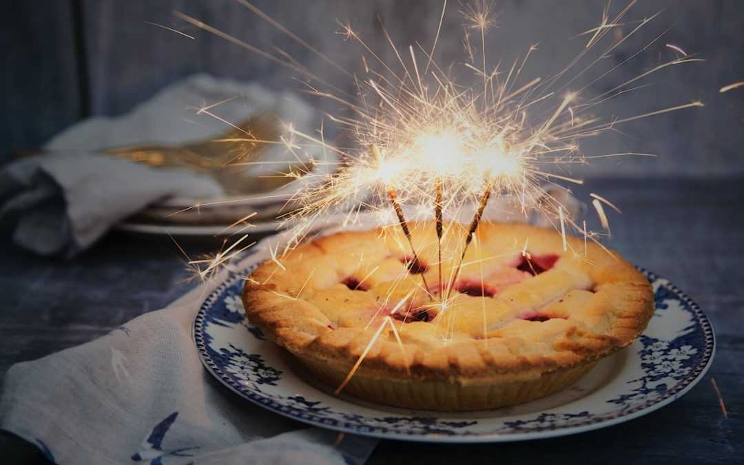 Apple pie with lit sparklers.